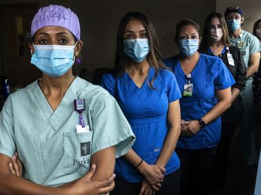 "From left, nurses Luyi Daniel, Perla Sanchez-Perez and Shasha Niederhaus, nurse and Senior Director of Surgical Services Kathleen Doherty, nurse Otto Madrigal, and Senior Vice President of Nursing and Surgical Services Samantha Rowley pose for a portrait just outside the Parkland Hospital COVID-19 Tactical Care Unit in Dallas. All but Niederhaus have been in the unit from the start of the pandemic, and they expressed some relief at their latest reality: a reduced number of patients now occupy single rooms after a spike in early July packed the unit with critically ill patients. ""Some are still very, very sick. There are just fewer of them,"" Rowley said. ""This lull is a reason for optimism."""