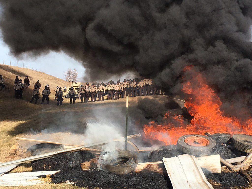 Tires burn as armed soldiers and law enforcement officers stand in formation on Thursday to force Dakota Access pipeline protesters off private land where they had camped to block construction. The pipeline is to carry oil from western North Dakota through South Dakota and Iowa to an existing pipeline in Patoka, Ill. (Mike McCleary/The Bismarck Tribune)