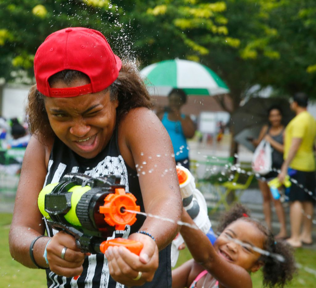 People squirt water on each other during a watergun flash mob at Klyde Warren Park in Dallas on July 15, 2017.  (Nathan Hunsinger/The Dallas Morning News)