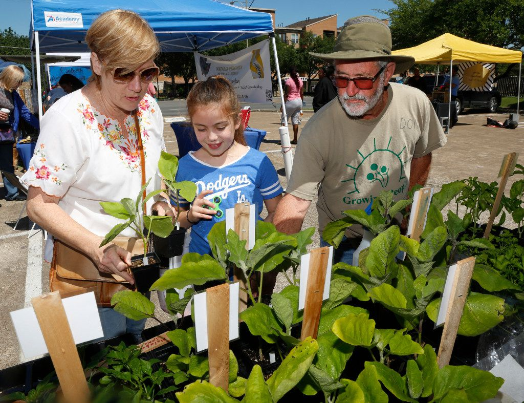 From left, Lori Martinez, Lola Martinez,10, and Don Lambert, from Gardeners in Community Development, discuss what plants are available at the Gardeners in Community Development booth at the White Rock Lake Farmers Market.