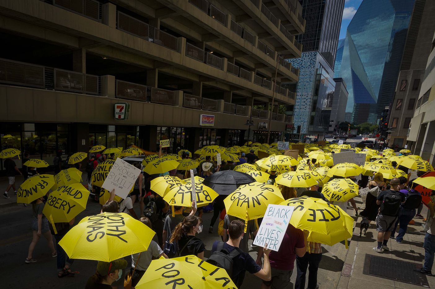 Demonstrators, many carrying umbrellas bearing the names of people who have been killed by police or racial violence, march through the streets of downtown Dallas following a rally commemorating Juneteenth at Dallas City Hall on Friday, June 19, 2020.