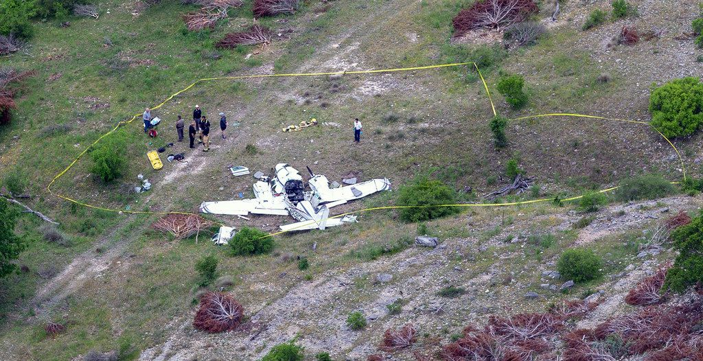 Authorities investigate at the crash scene of a twin-engine Beechcraft BE58, Monday, April 22, 2019, near Kerrville, Texas.