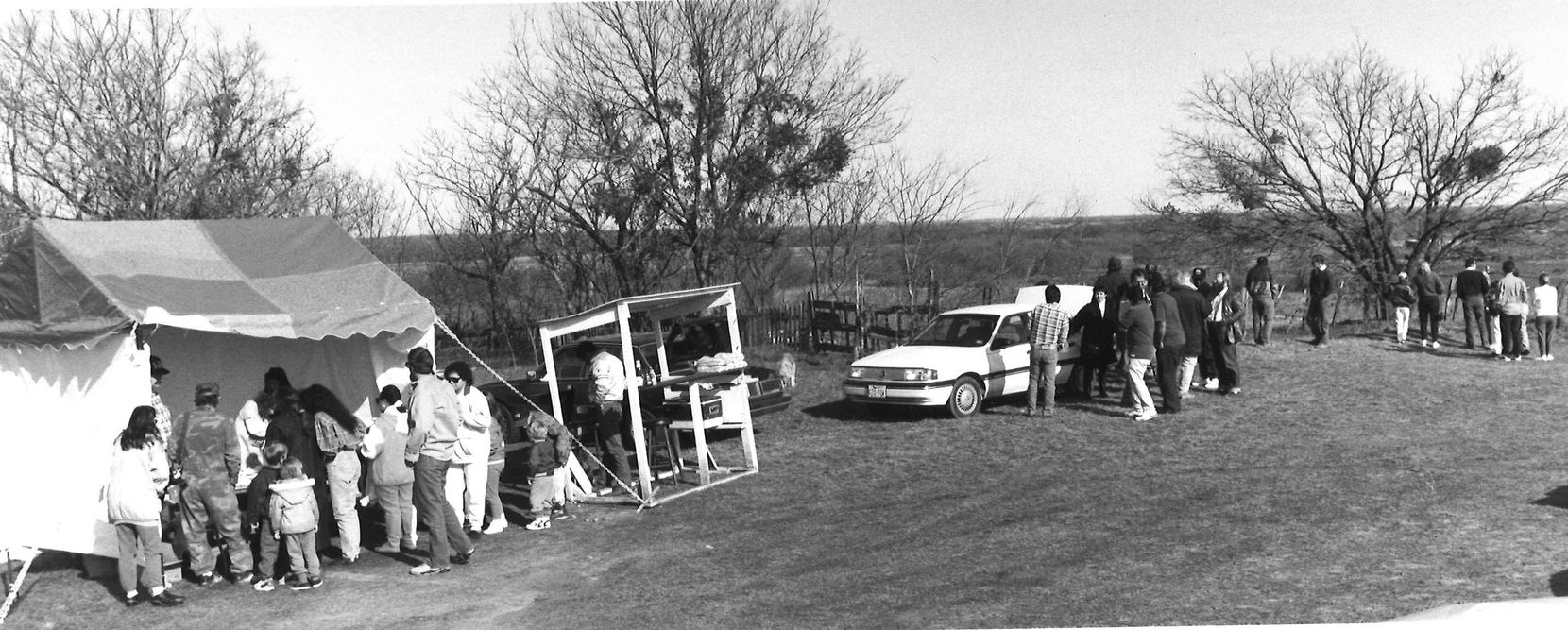 """March 12, 1993: Vendors sell merchandise to onlookers in Waco. The tent on the left sold T-shirts, while the booth in the middle served """"Koresh Burgers and Dogs."""" Rosaline Eastepp sold T-shirts out of the white car."""