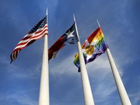 In honor of Pride Month, the City of Dallas' Pride flag (right) flies alongside the Texas and U.S. flags outside of City Hall in downtown Dallas, Thursday, June 18, 2020.