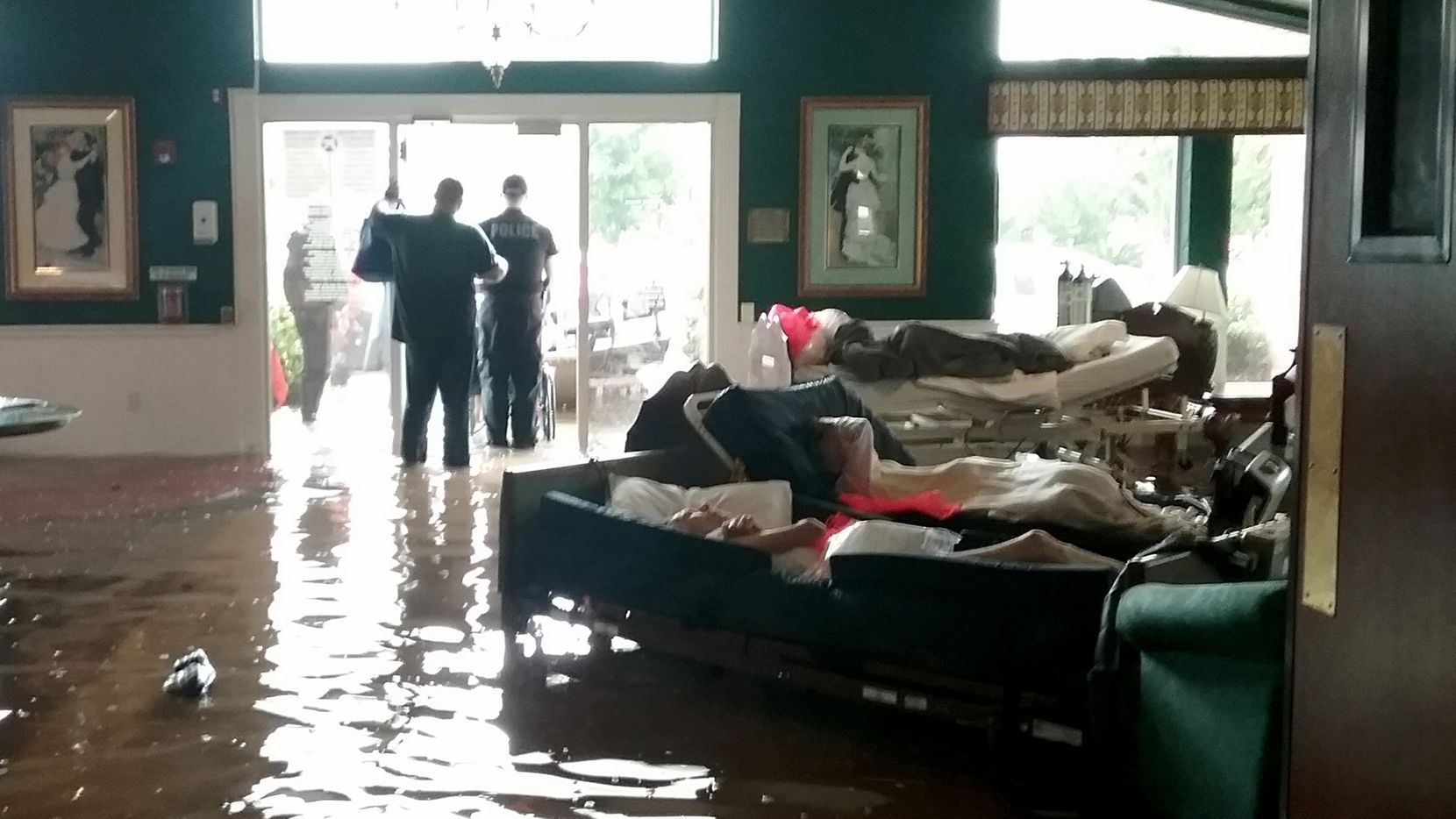 Residents lay on sofas waiting to be evacuated from the Cypress Glen senior care facility in Port Arthur last year. The care center was inundated with water from Hurricane Harvey. Cypress Glen is owned by Dallas-based Senior Care Centers. (Matt Pearce/Los Angeles Times)