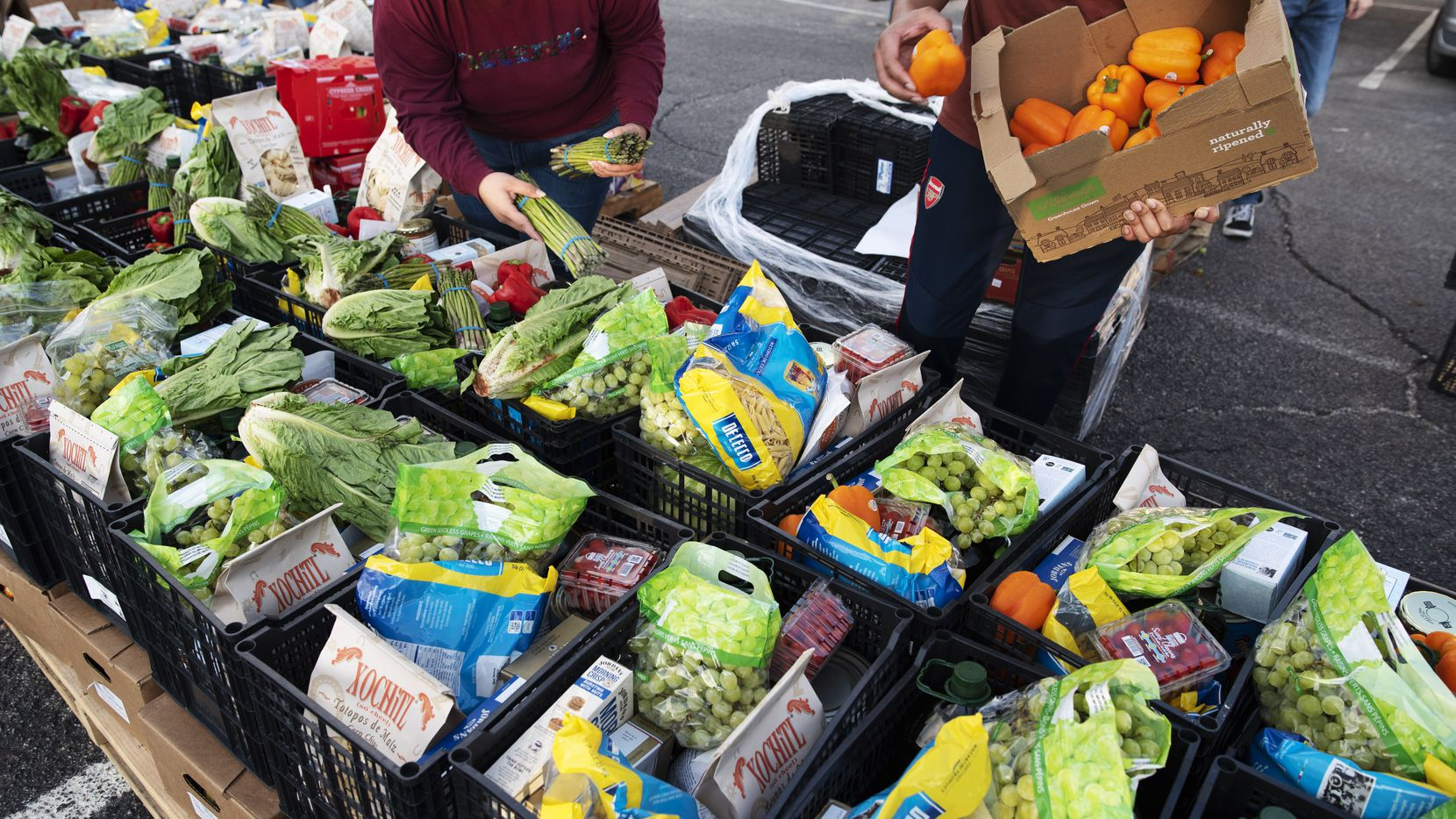 Volunteers helped unload and pack food supplies for families during a drive-through event hosted by Harvest Project Food Rescue and the North Texas Dream Team last July outside of East Grand Preparatory in Dallas.