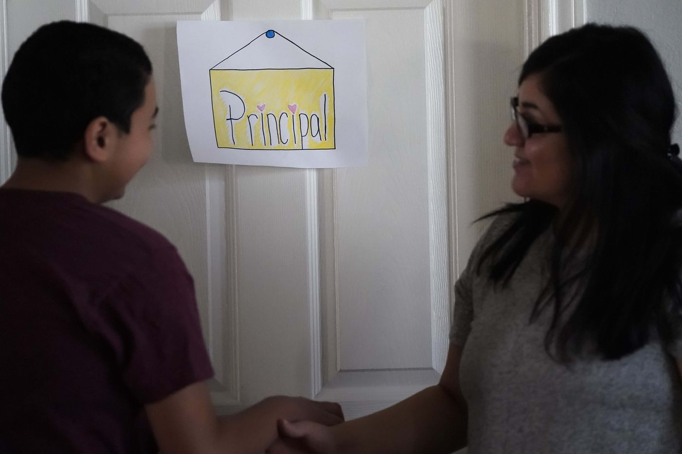 "Francisco Cabrera, 13, jokes with his mother Nancy Segovia-Cabrera outside the ""principal's off'ice,"" otherwise known as his parents' bedroom, at the family's home in Grand Prairie. The Cabrera family, like many around North Texas, suddenly has four youngsters at home with mom acting as ""principal"" making sure they all complete assignments."