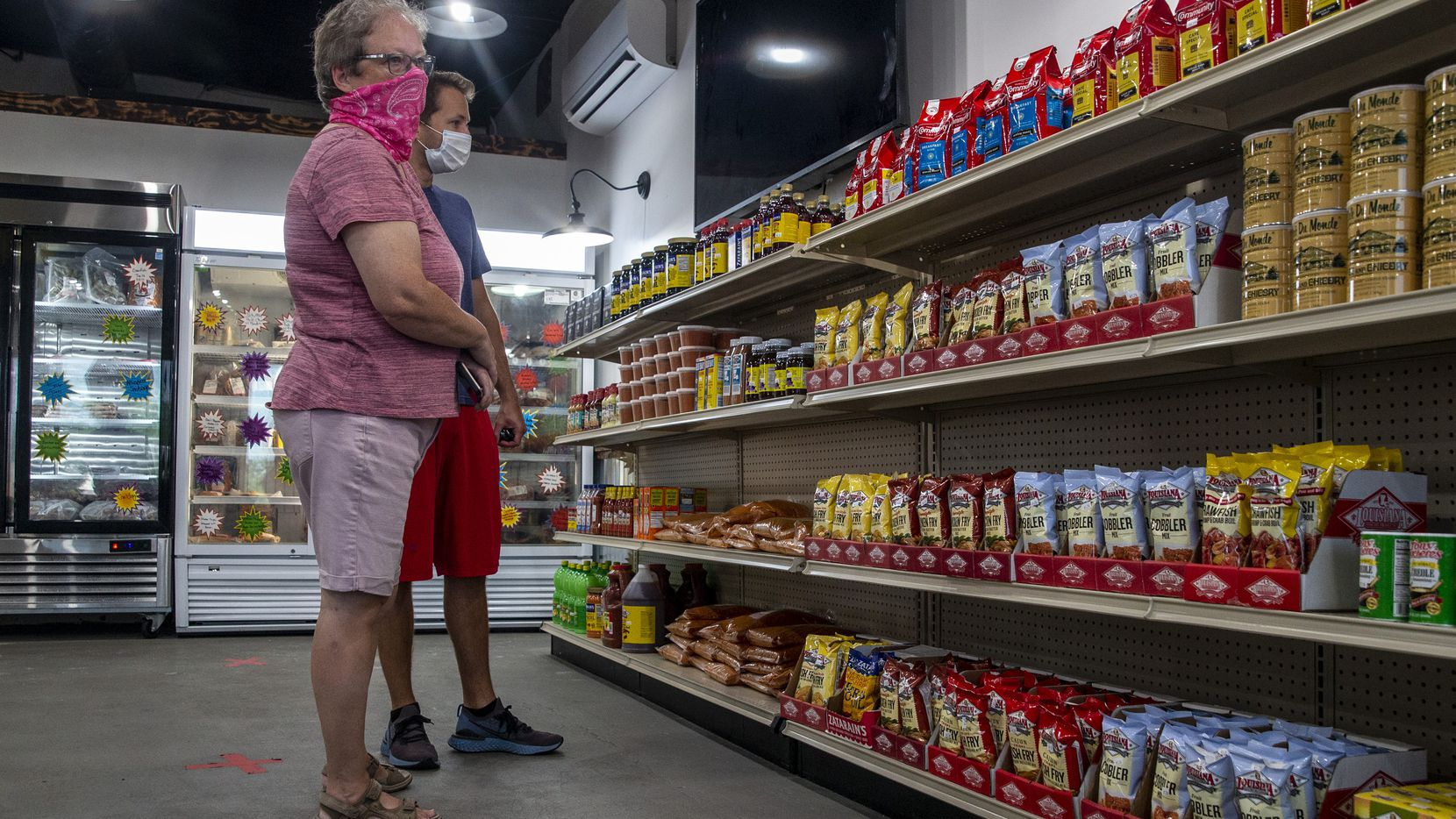 Cindy Brachey and her son, Tommy, peruse the market cajun convenience items kept in stock at T-JohnnyÕs Seafood and Cajun Market in Colleyville, Texas, on Wednesday, July 8, 2020. The establishment has experienced considerable success despite launching in the middle of the COVID-19 pandemic Ñ something owner Phil Tullis attributes to their dedication to authenticity. ÒThese are recipes we grew up with as kids,Ó said Tullis, who hails from Louisiana. ÒMy aim is to provide taste from back home. This is comfort food to a lot of people, especially in a time like this.Ó (Lynda M. Gonzalez/The Dallas Morning News)