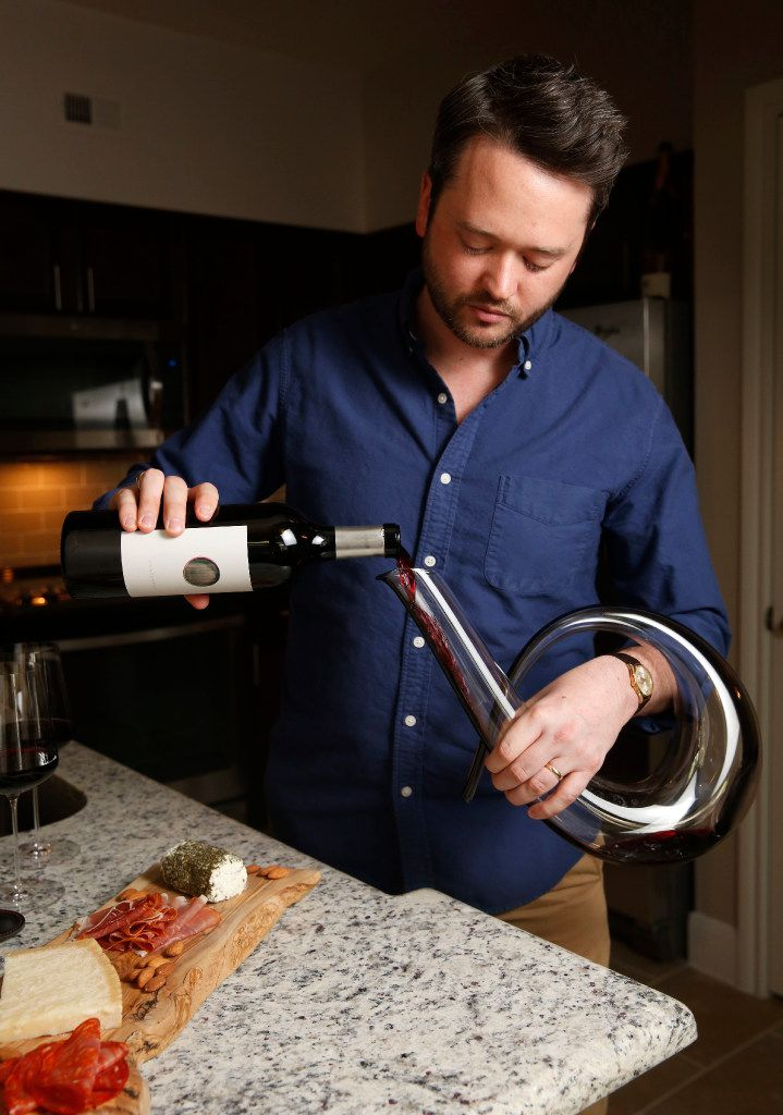 Michael Kennedy, founder of Component Wine Co., pours wine into a decanter at his home in Dallas. (Rose Baca/The Dallas Morning News)