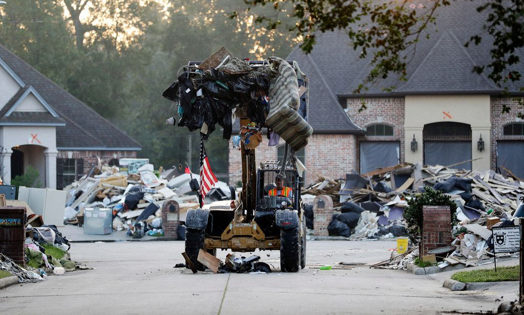 A worker cleans up debris in a neighborhood flooded by Hurricane Harvey in Beaumont in September, 2017. If House Republicans have their way, victims of hurricanes in Texas and Florida could deduct their losses on their taxes. But victims of the California wildfires no longer could.