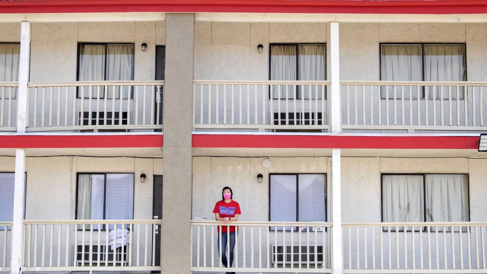 Joie Lew, an 18-year-old freshman at SMU, poses for a portrait outside the OYO Hotel suite where she lives with her divorced parents during the coronavirus pandemic.