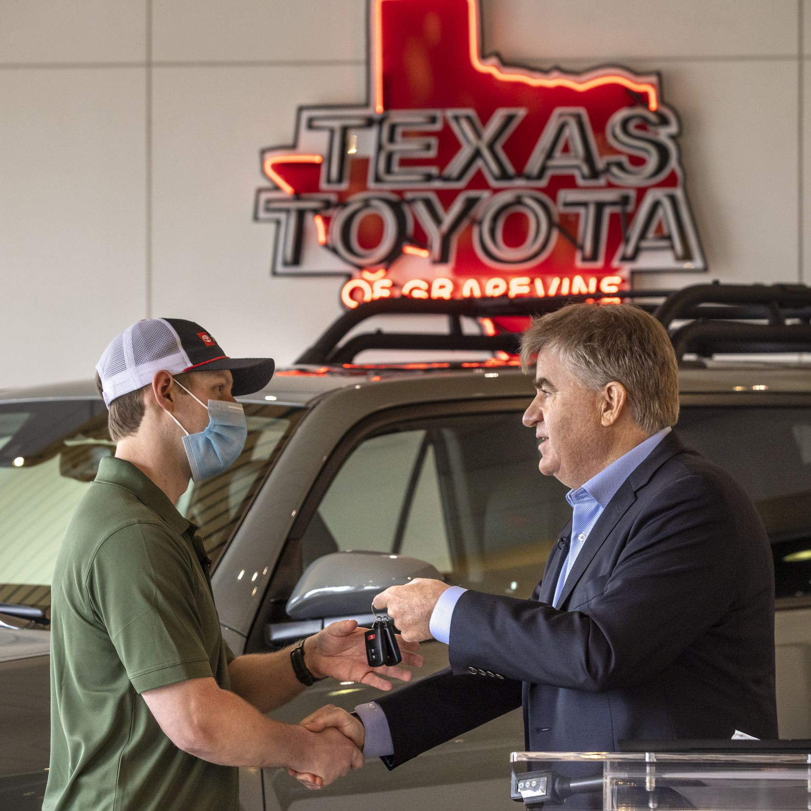 Bob Carter (right), executive vice president of sales for Toyota Motor North America, presents the keys to a 2021 Toyota 4Runner TRD Pro to EMT Trey McDaniel at the Texas Toyota of Grapevine dealership on Thursday, Feb. 25, 2021, in Grapevine, Texas.