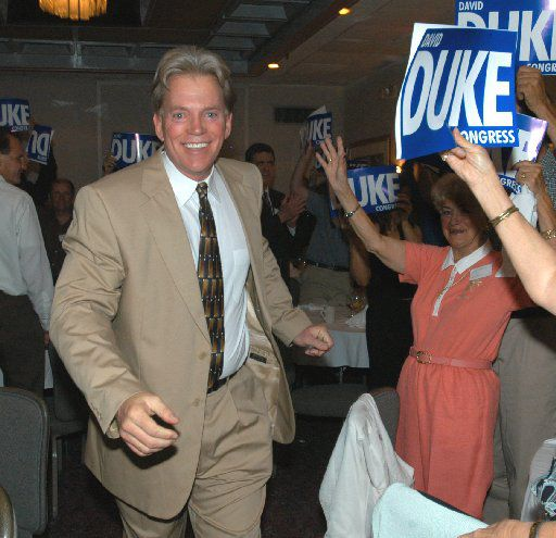 """David Duke enters a room of supporters in Kenner, La., on May 29, 2004.  Fresh out of prison for bilking supporters, Duke hosted a weekend gathering of enthusiastic backers eager to hear him as he lashed out at Jews, blacks, immigrants and the """"Zionist-controlled media.''"""