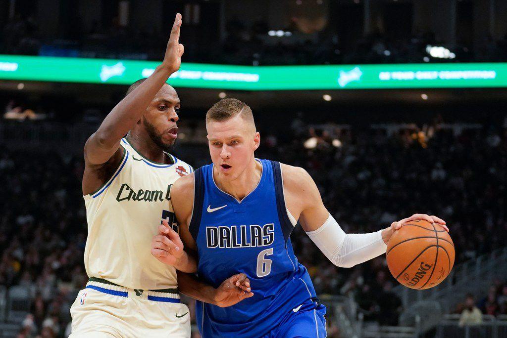 Dallas Mavericks' Kristaps Porzingis tries to drive past Milwaukee Bucks' Khris Middleton during the first half of an NBA basketball game Monday, Dec. 16, 2019, in Milwaukee.