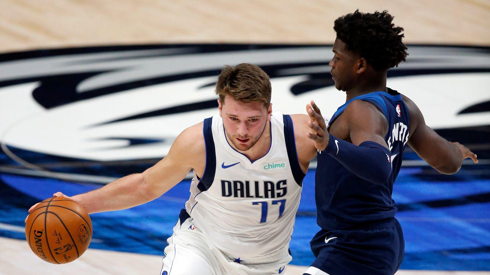 El jugador de los Dallas Mavericks, Luka Doncic (77), es custodiado por un jugador de  Minnesota Timberwolves en el juego de pretemporada del 17 de diciembre de 2020 en el American Airlines Center de Dallas.