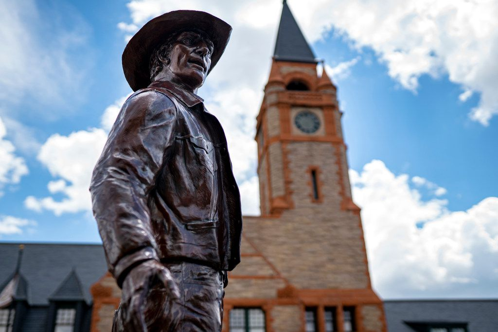A bronze statue of a cowboy stands in front of the Depot, known for local music performances and farmers markets, in Cheyenne, Wyo.