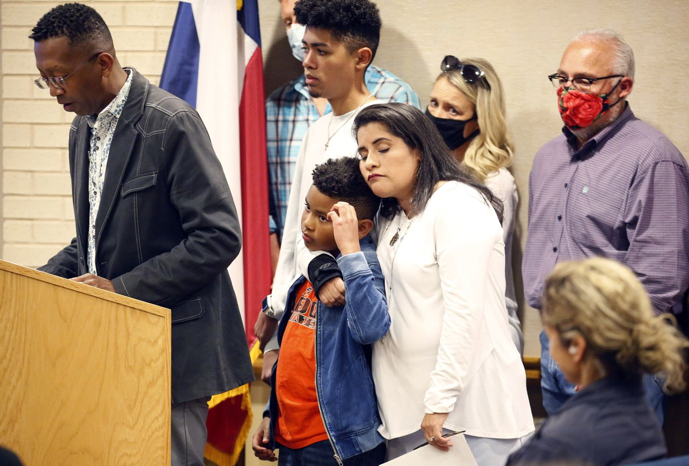 Parent Maria Turner hugs one of her two boys after telling the Aledo ISD school board about what happened after moving to Aledo, Monday, April 19, 2021. The boys were playing a friendly game of 'cops and robbers' when it became physical. An alternation in which another boy told his friend to kneel on her son's neck after being tackled to the concrete. Her husband, Raymond Turner (left), also spoke. (Tom Fox/The Dallas Morning News)