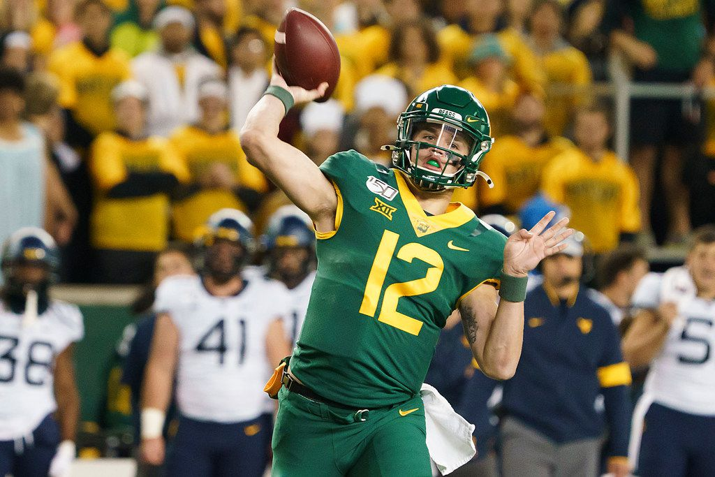 Baylor quarterback Charlie Brewer (12) throws a 13-yard touchdown pass to  wide receiver R.J. Sneed during the first half of an NCAA football game against the West Virginia at McLane Stadium on Thursday, Oct. 31, 2019, in Waco, Texas.