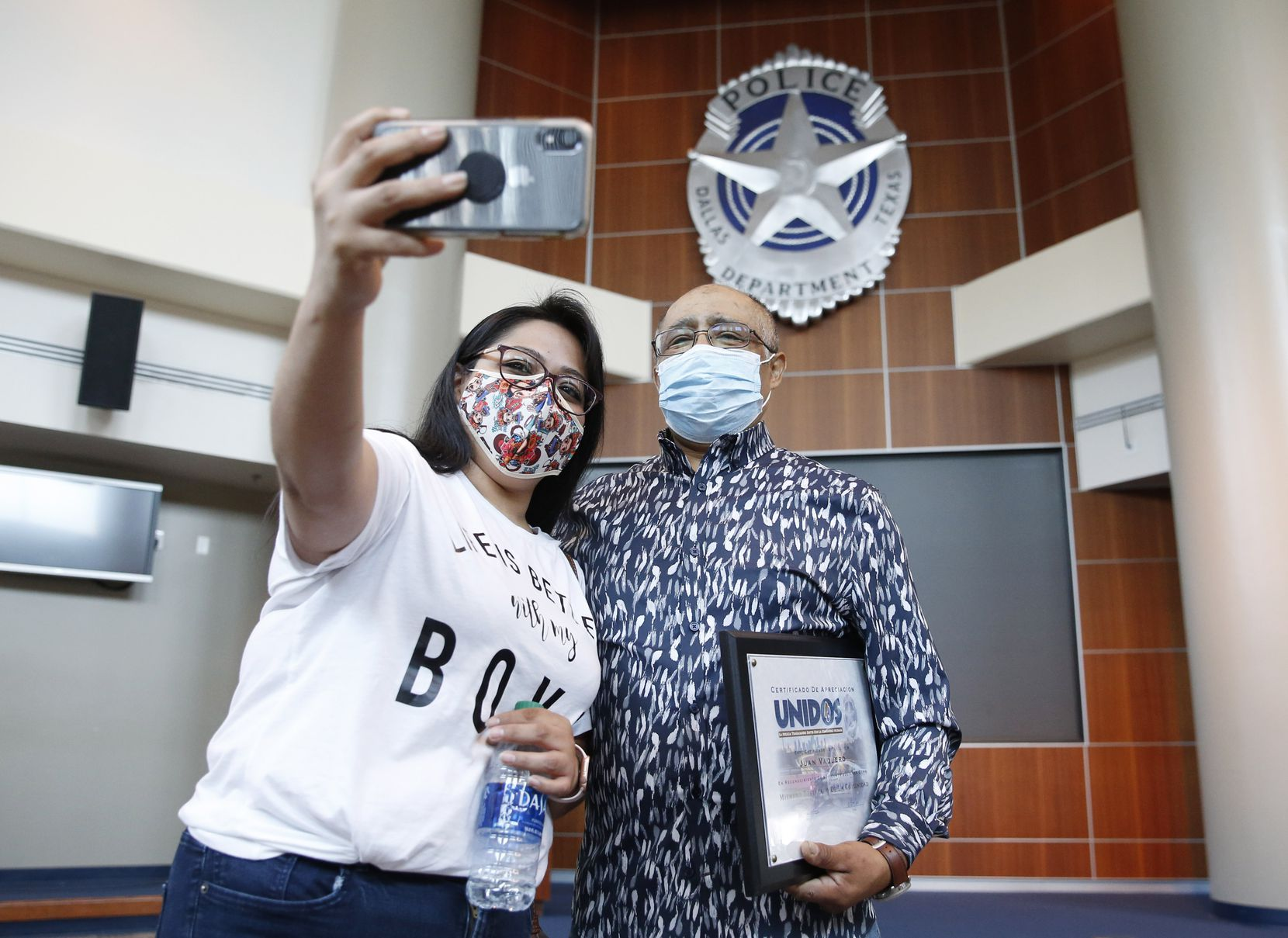 Norma Rocha takes a photo with her father, Juan Vaquero, who is holding a certificate he received from the Dallas Police Department during a ceremony at headquarters in May. Police thanked Vaquero for making the call that led to his 6-year-old neighbor's rescue.