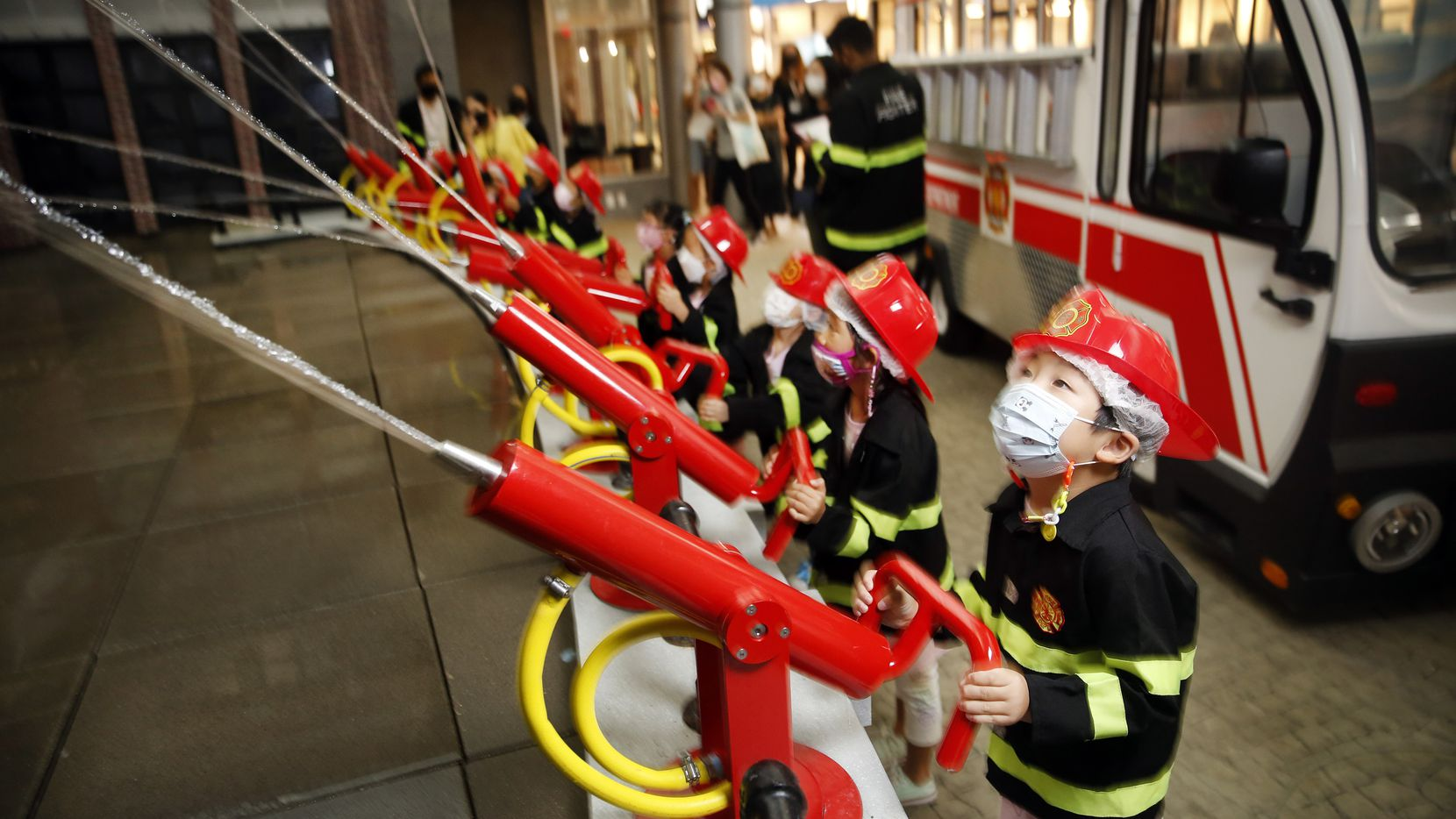 Children dressed as firefighters spray water hoses on a match factory at KidZania at Stonebriar Centre in Frisco, the company's only United States location.
