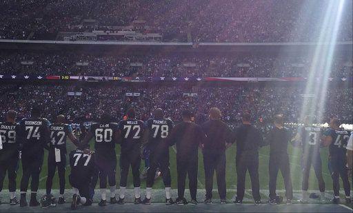 El jugador de los Jaguars de Jacksonville, Patrick Omameh (77), cuarto de la izquierda, se hinca durante el toque del himno nacional antes de un partido de la NFL contra los Ravens de Baltimore, en Wembley Stadium en Londres. Foto AP.