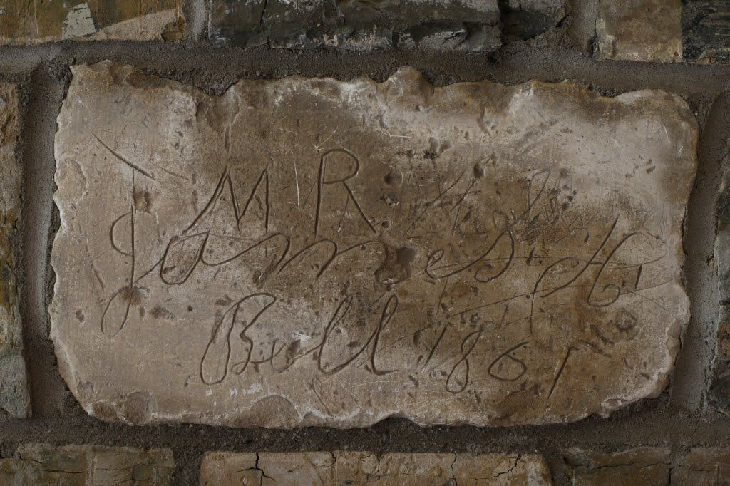 An inscription is carved into a brick on the fireplace at Collinwood House in Plano.