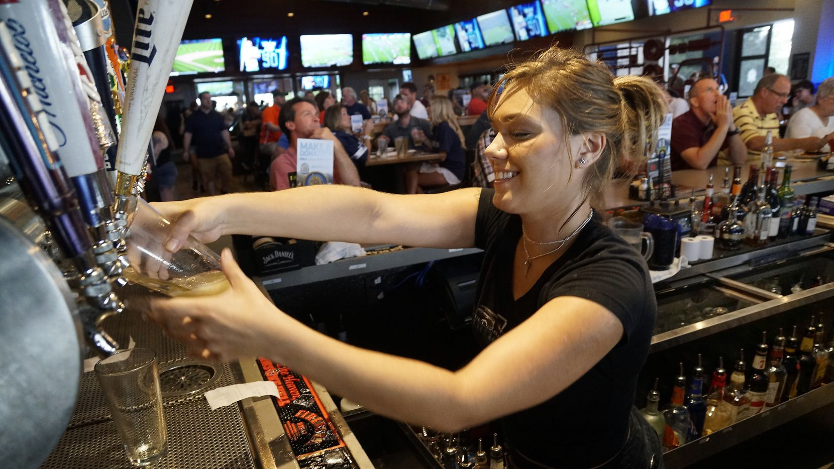 Bartender Tesla Silva waits on customers at BoomerJack's in Grapevine. The city's restaurants and bars reported more than $8 million in alcohol sales in May, up over 70% since the state fully reopened.
