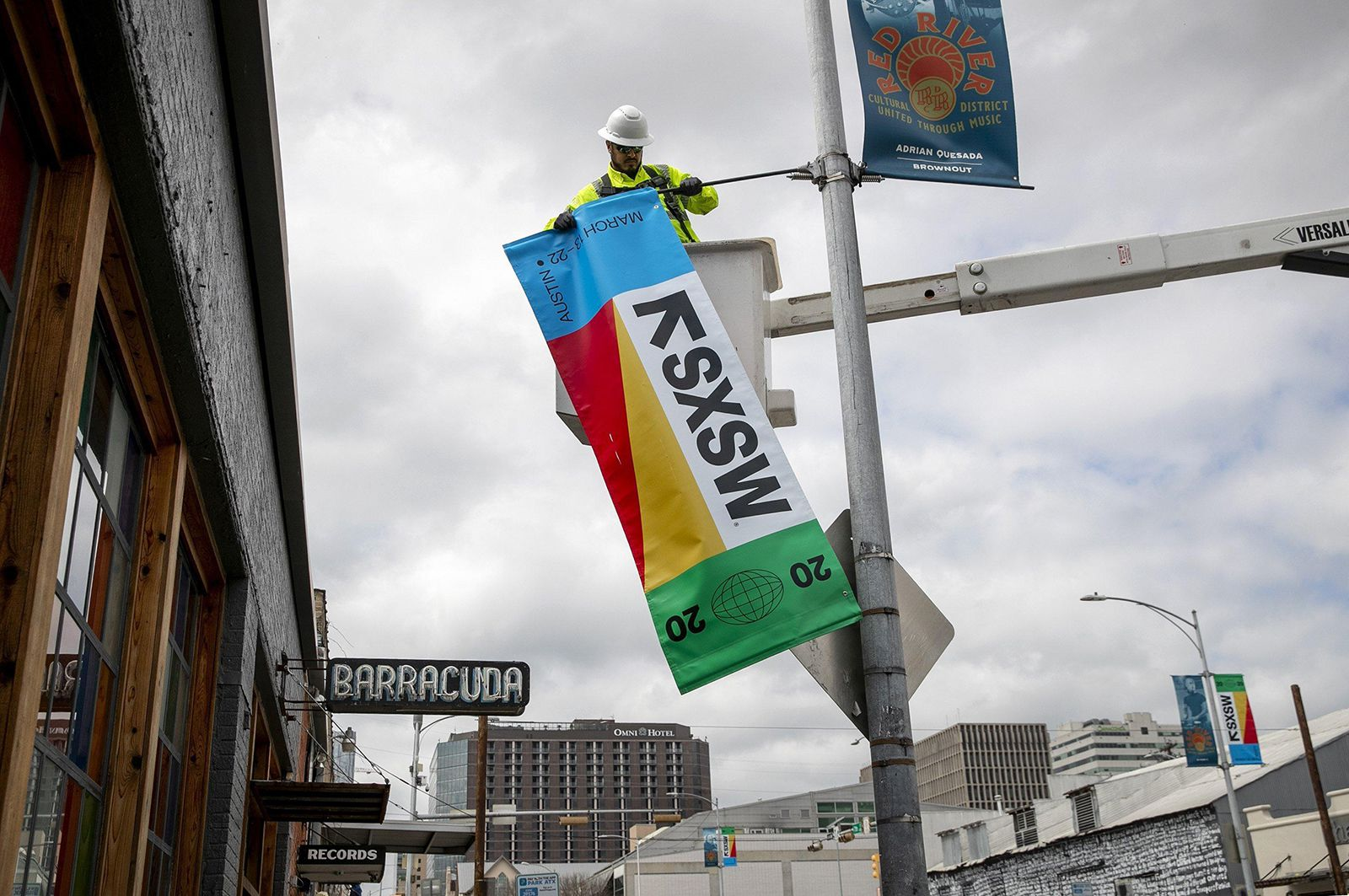 David Rodriguez, with the city of Austin's transportation department, takes down a South by Southwest banner on East 7th Street in Austin on Tuesday, March 24.