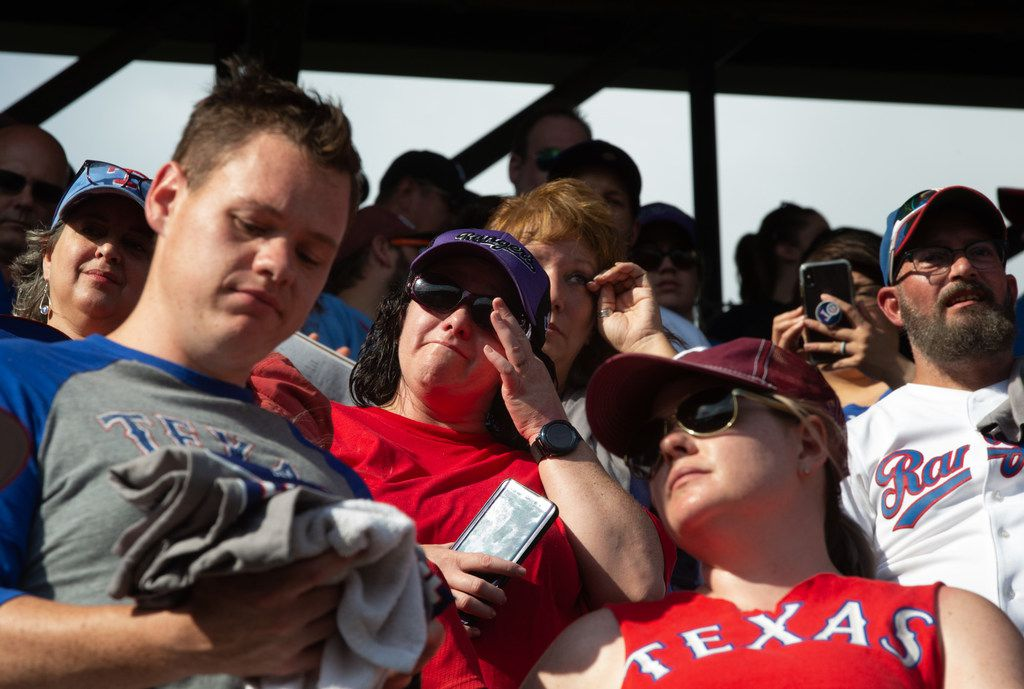 Fans wipe away tears at the conclusion of the Texas Rangers' final game ever played at Globe Life Park in Arlington, Texas, on Sunday, Sep. 29, 2019. Following the game, fans enjoyed a ceremony and parade to place home plate at the new, adjacent Globe Life Field.