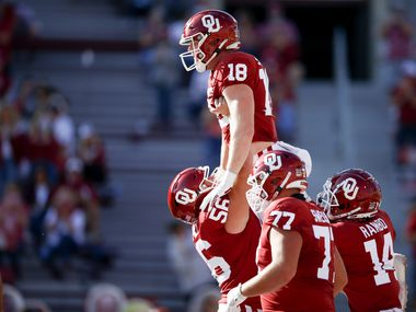 Oklahoma offensive lineman Creed Humphrey (56) lifts tight end Austin Stogner (18) after Stogner's touchdown catch against Kansas during a game in Norman, Okla., on Saturday, Nov. 7, 2020. (Ian Maule/Tulsa World via AP)