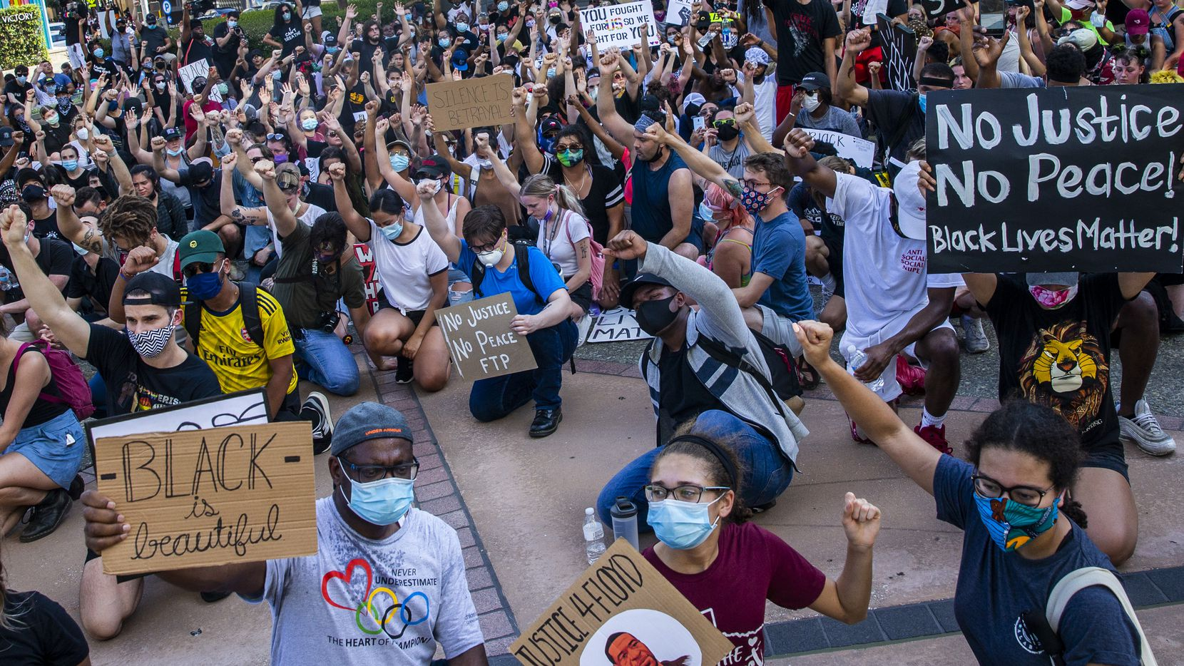 James Akemba (left) and his daughters Alexis (center), 16, and Jasmine, 15, join other protesters in taking a knee during a demonstration in front of the American Airlines Center to denounce police brutality and systemic racism in Dallas on Thursday, June 4, 2020. The demonstration took place on the seventh consecutive day of organized protests in response to the recent deaths of George Floyd in Minneapolis and Breonna Taylor in Louisville.
