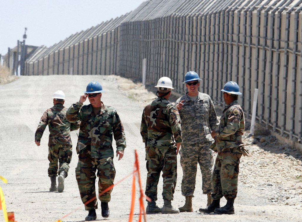 In this June 21, 2006, file photo, members of the California National Guard work next to the U.S.-Mexico border fence near the San Ysidro Port of Entry in San Diego. President Donald Trump said April 3, 2018, he wants to use the military to secure the U.S.-Mexico border until his promised border wall is built.