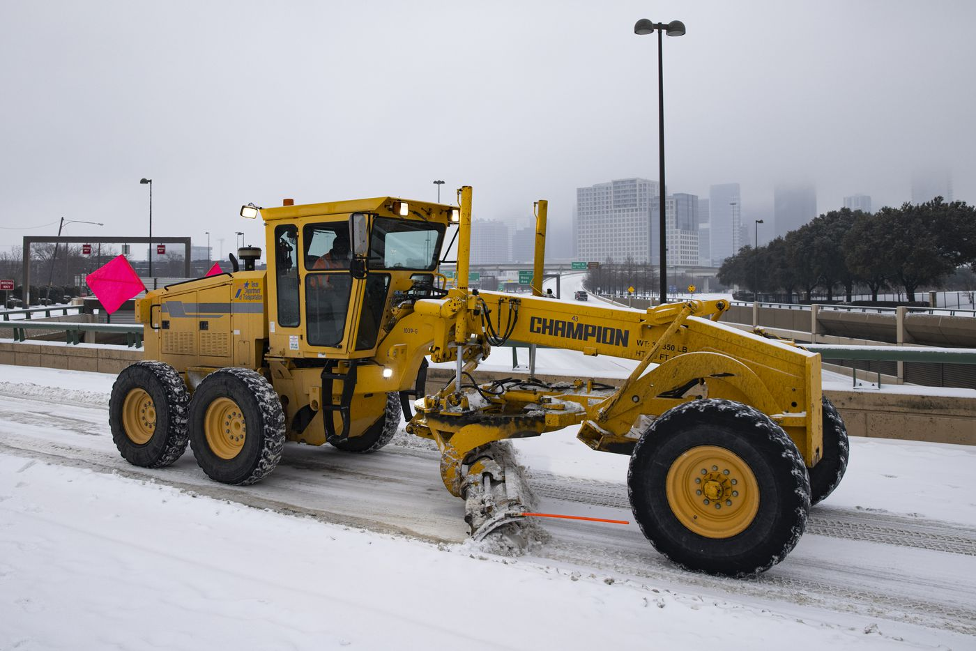 A TxDOT snowplow clears snow from N Hall St over North Central Expressway in Dallas on Wednesday, Feb. 17, 2021. Millions of Texans have lost power amid this record-breaking winter storm.
