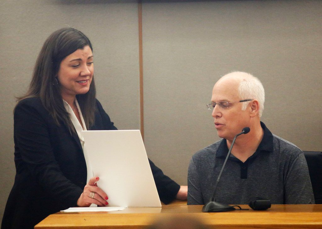 Prosecutor Andrea Moseley shows Mark Stevens a wedding photo of his brother Dave and Patti Stevens  on the stand during the punishment portion of Thomas Johnson's murder trial.