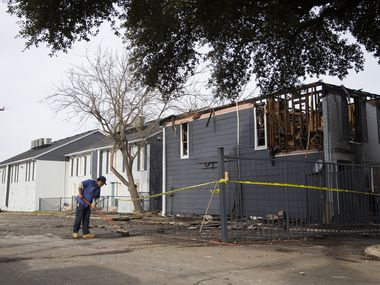 A worker begins to clean up the damage at Chase Place Apartments after a fire displaced approximately 30 residents on Dec. 5, 2019 in Northwest Dallas.