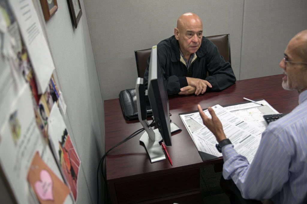 Homeowner Joe Lara (center) discusses an increase in his property taxes with William Ibrahim, a residential appraiser with the Dallas Central Appraisal District (G.J. McCarthy/The Dallas Morning News)