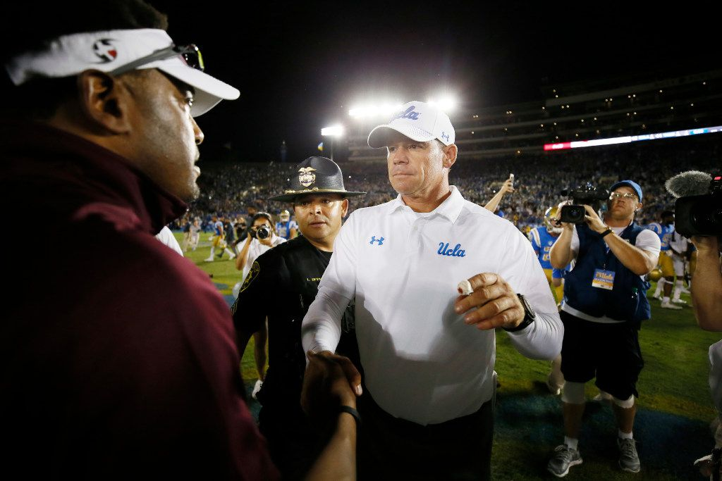 UCLA head coach Jim Mora, right, shakes hands with Texas A&M head coach Kevin Sumlin, left, after an NCAA college football game, Sunday, Sept. 3, 2017, in Pasadena, Calif. UCLA won 45-44. (AP Photo/Danny Moloshok)