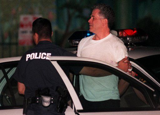 Police take John Battaglia into custody in the shooting deaths of his daughters.