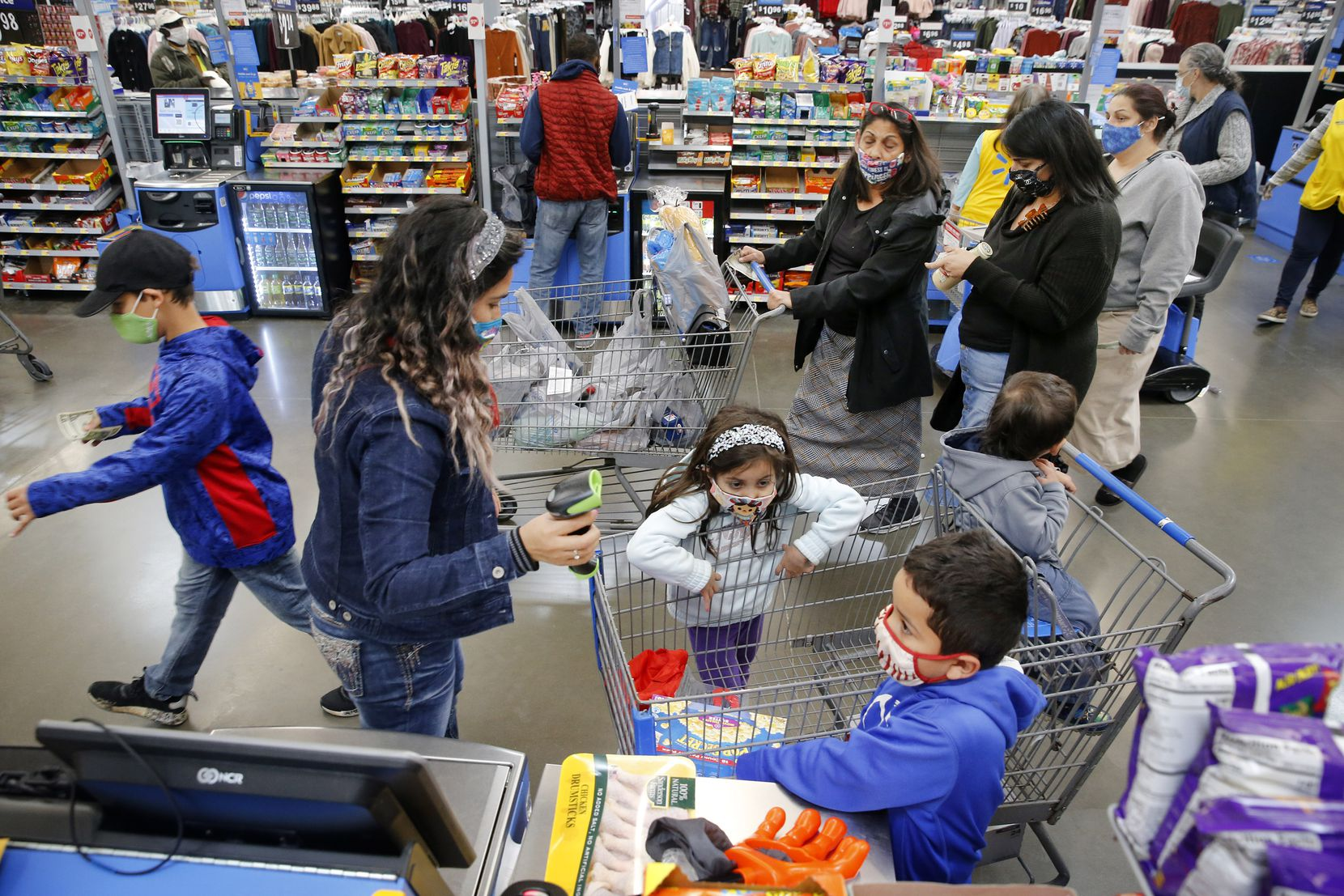 Shopper Evelin Huerta of Zapata, Texas and her children use a Scan & Go self checkout at the Walmart Supercenter on Lyndon B Johnson Freeway in Dallas, Thursday, October 29, 2020. (Tom Fox/The Dallas Morning News)