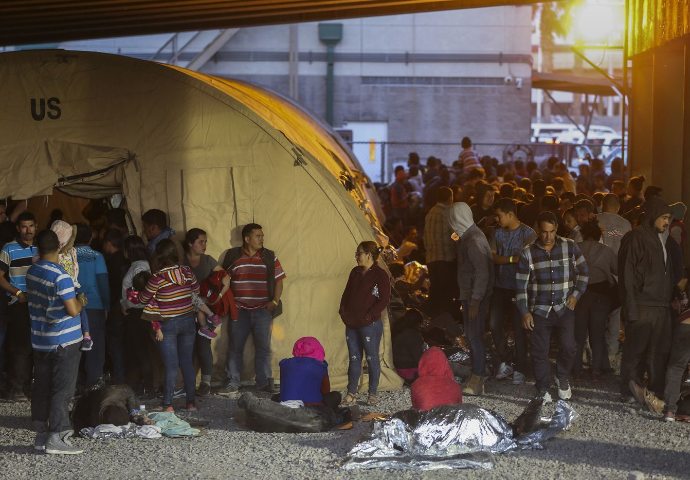 Some migrants slept outside on gravel, provided only thin Mylar blankets for warmth.