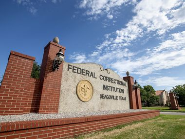 A sign marks the entrance to the Federal Correctional Institution in Seagoville, where there has been an outbreak of COVID-19.