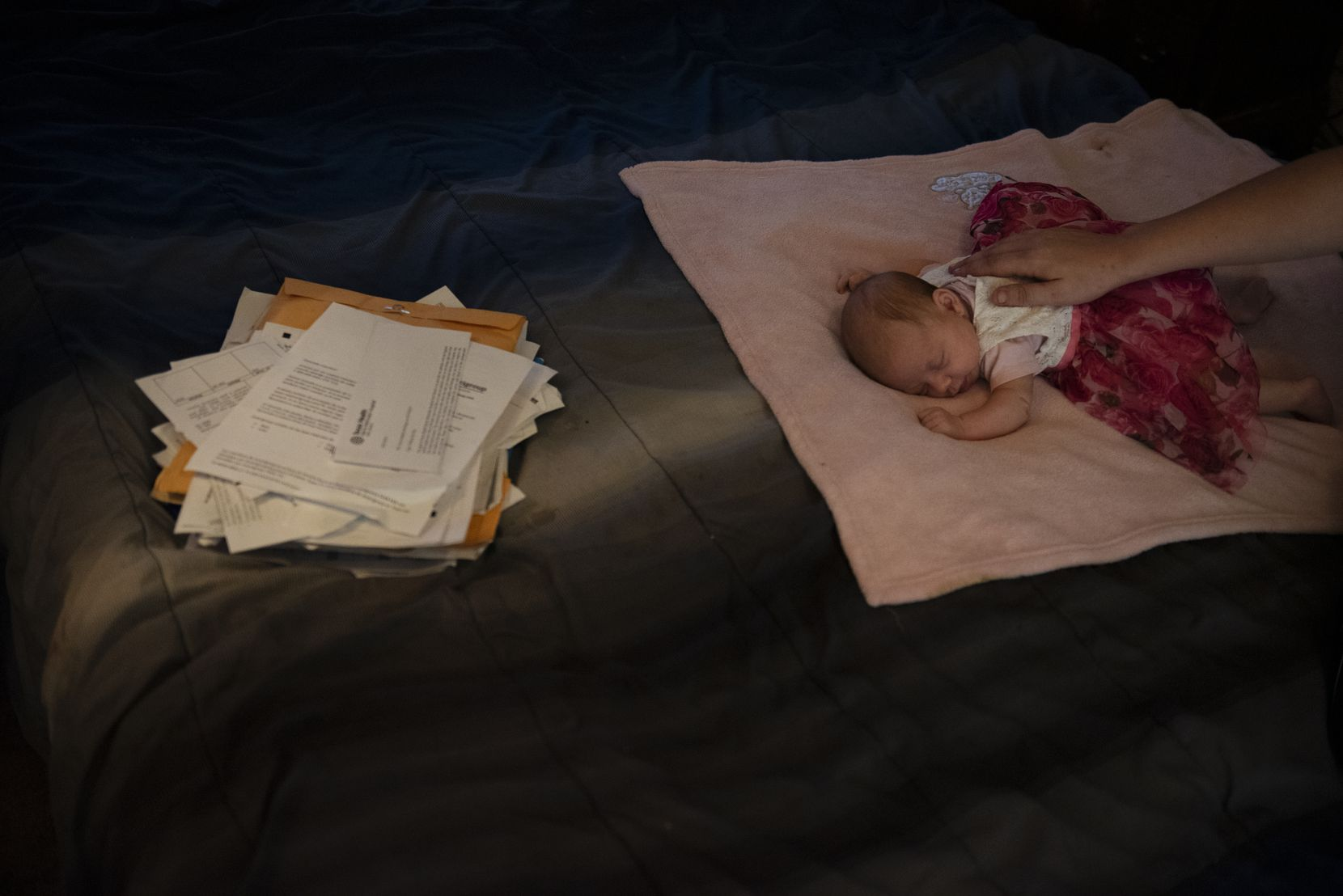 Tiffany Revilla strokes her newborn daughter's back as the baby sits next to a pile of medical bills at their home.
