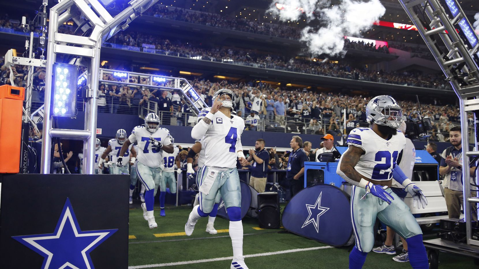 Dallas Cowboys quarterback Dak Prescott (4), Dallas Cowboys running back Ezekiel Elliott (21) and players take the field as they are introduced before playing against the Buffalo Bills at AT&T Stadium in Arlington, Texas on Thursday, November 28, 2019.