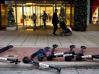 Bird rental scooters lie on the ground outside the Neiman Marcus store in downtown Dallas