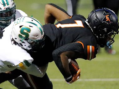 Lancaster wide receiver Phaizon Wilson is tackled by Carrollton Newman Smith defensive back Paul Calander during a game on October 16, 2020. (Stewart F. House/Special Contributor)