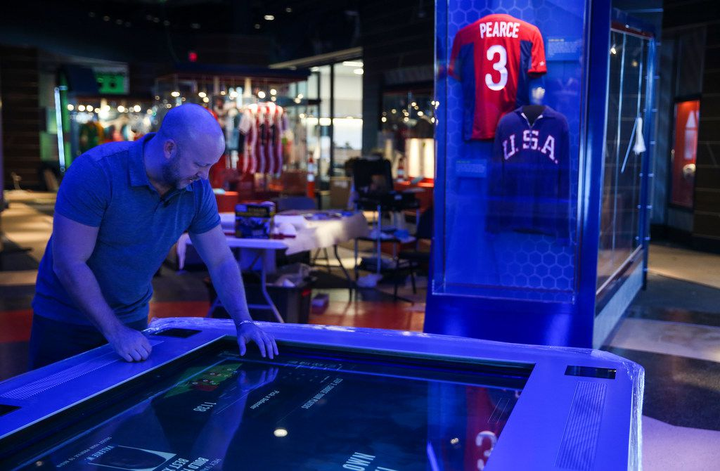 """National Soccer Hall of Fame executive director Djorn Buchholz interacts with a """"Build Your Own Best XI"""" exhibit."""