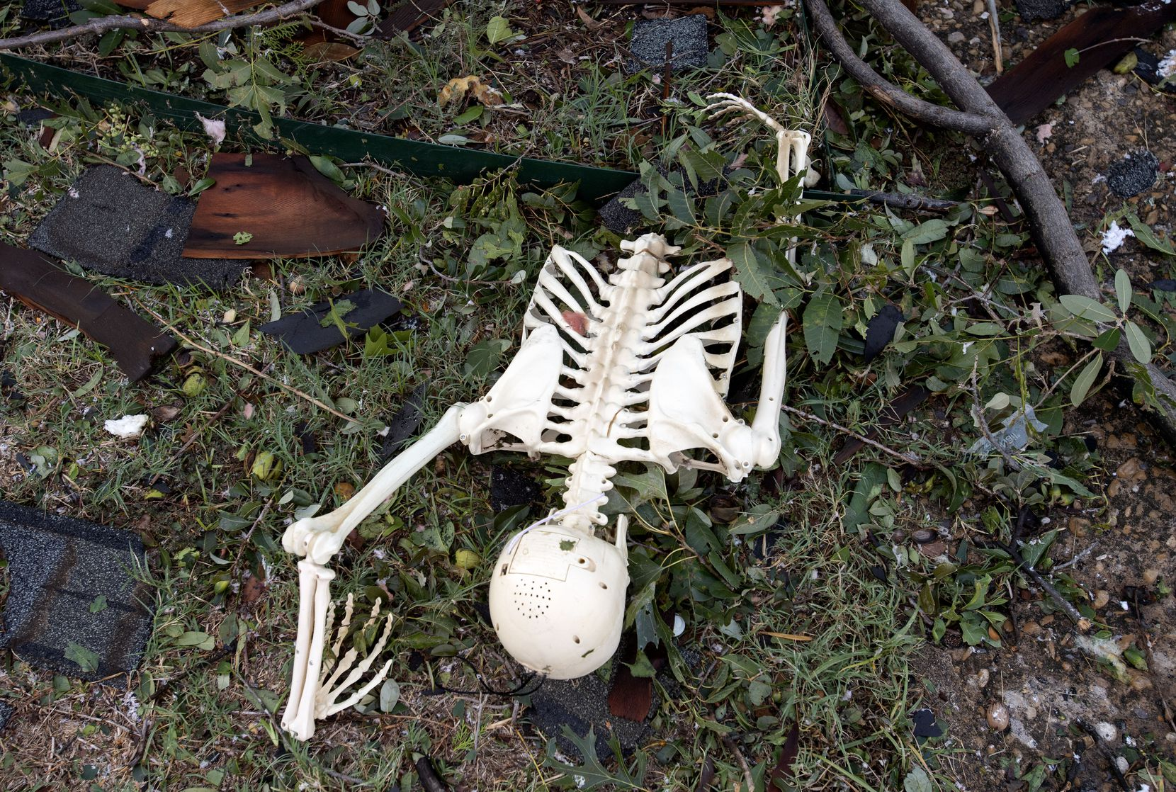 A Halloween decoration fake skeleton lies amid debris in the front yard of Brett and Madeline Murack on Crestover Circle after Sunday night's tornado on Monday, Oct. 21, 2019 in Dallas.