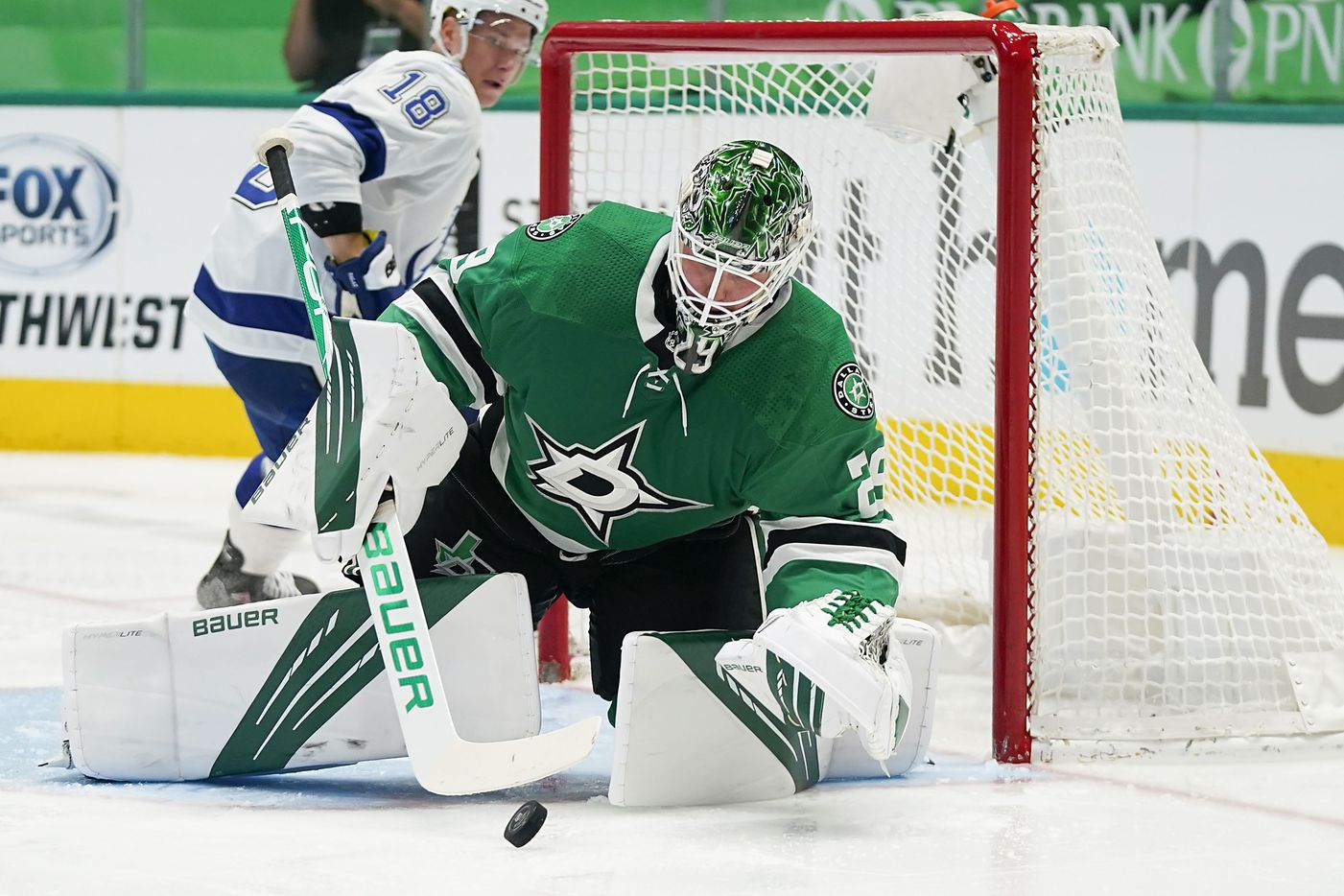 Dallas Stars goaltender Jake Oettinger covers up the puck in front of Tampa Bay Lightning left wing Ondrej Palat (18) during the second period of an NHL hockey game at the American Airlines Center on Thursday, March 25, 2021, in Dallas. (Smiley N. Pool/The Dallas Morning News)