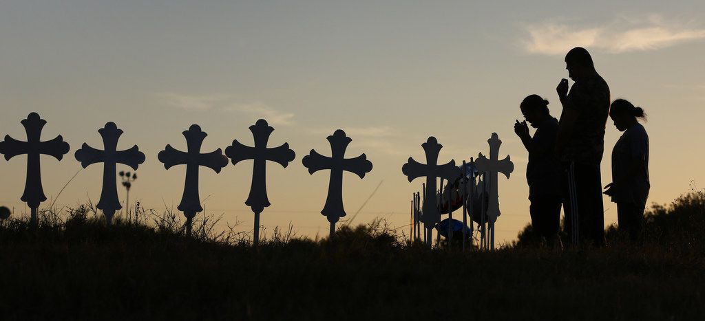 Irene and Kenneth Hernandez and their daughter Miranda say a prayer in front of the 26 crosses placed in a field in Sutherland Springs to honor those killed in Sunday's church shooting.