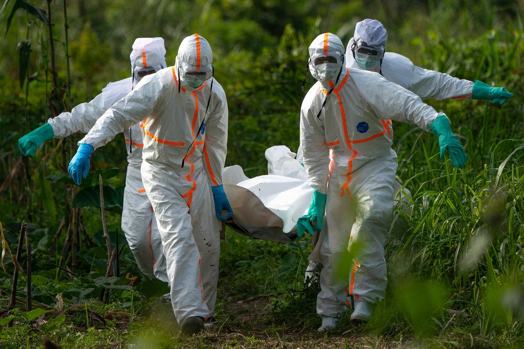 Burial workers dressed in protective gear carried the remains of an Ebola victim in July in Beni, Congo.
